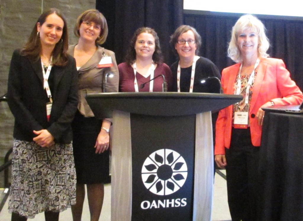 CLRI staff standing around the OANHSS Conference podium