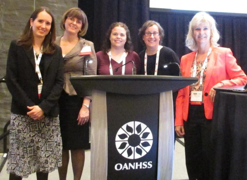 CLRI staff standing around the OANHSS Conference podium