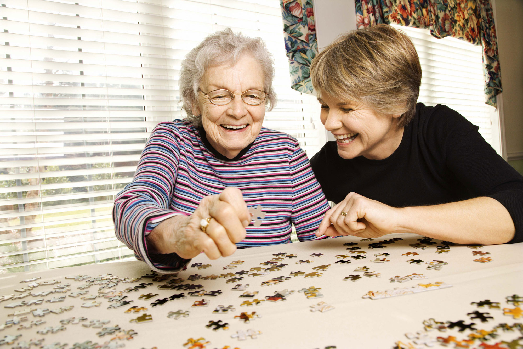 Senior and daughter working on a puzzle.