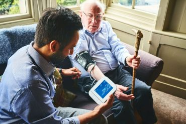 Health care worker checking blood pressure of older man sitting in chair