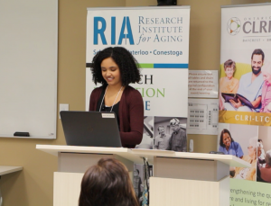 Co-op student Kyla morgan stands at a podium with an RIA stand-up banner and an Ontario CLRI stand-up banner in the background