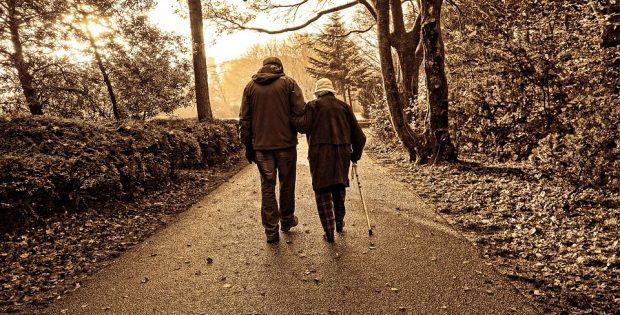 Olde couple walking down an autumn trail
