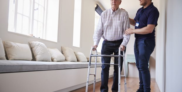 Senior man using a walking frame with male personal support worker at home