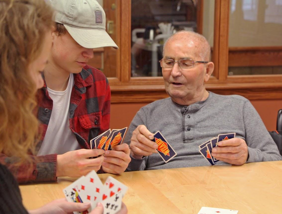 senior man and teenage boy and girl playing cards