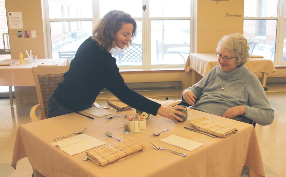 senior-woman-and-teenage-girl-dining-table