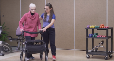 senior woman with walker and female student assisting mobility