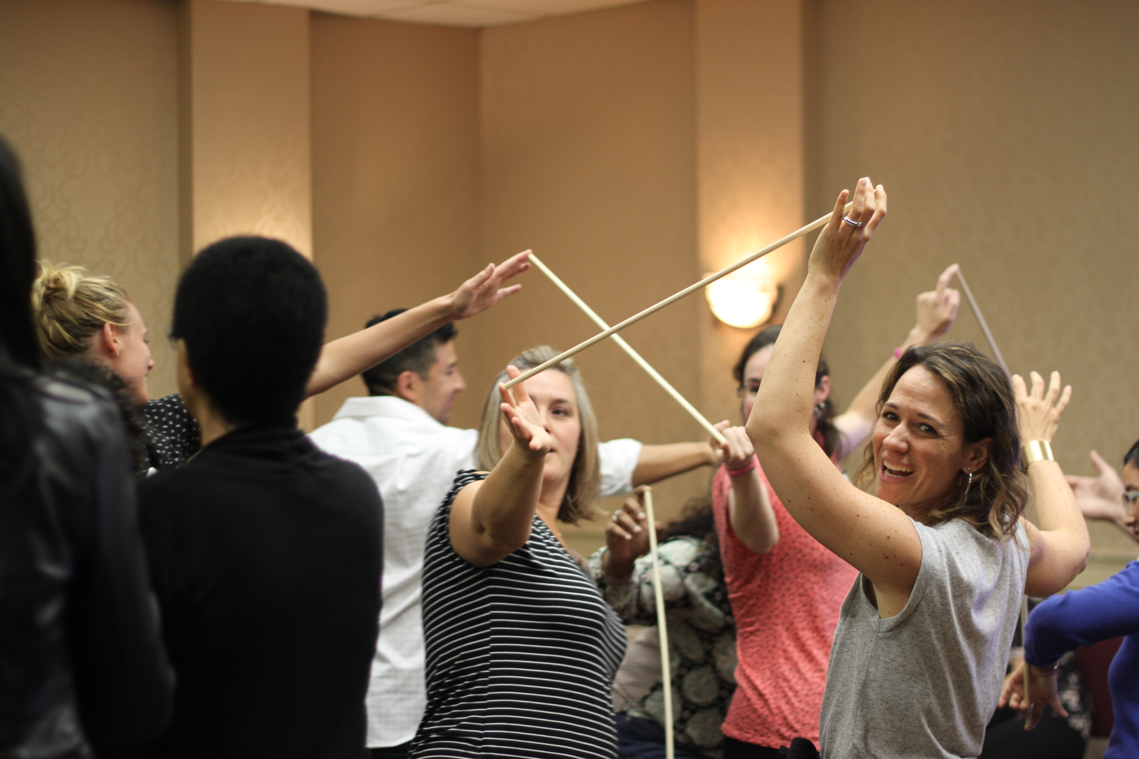 A group of women in a room work together to hold sticks in the air