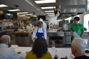 Participant discuses her dish to a panel of judges